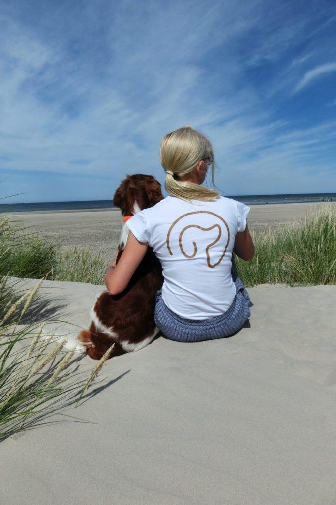 Sandra Dehli sitz mit ihrem Hund auf einer Düne. Sie hat den Arm um ihn gelegt.