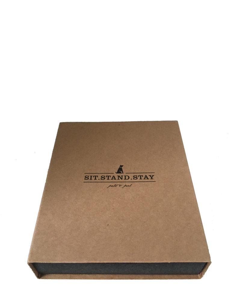Die Verpackung des Hundehalsbandes ist ein hellerbrauner Schubkarton von sit-stand-stay.