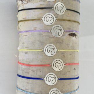 Armbänder in verschiedenen Farben. Ein Hundekopf ist in einem runde Silberplättchen ausgeschnitten.