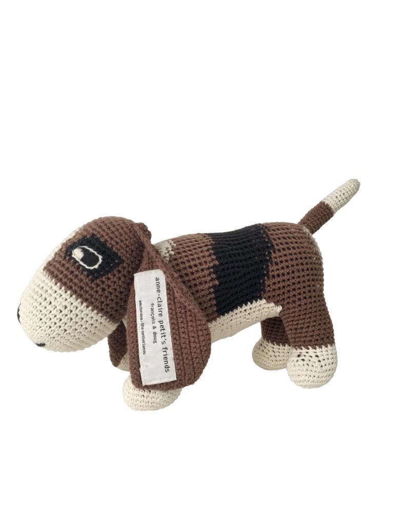 Ein gehäkelter Hund, ein Basset von Anne-Claire Petit Er ist beige, braun, schwarz gefleckt.