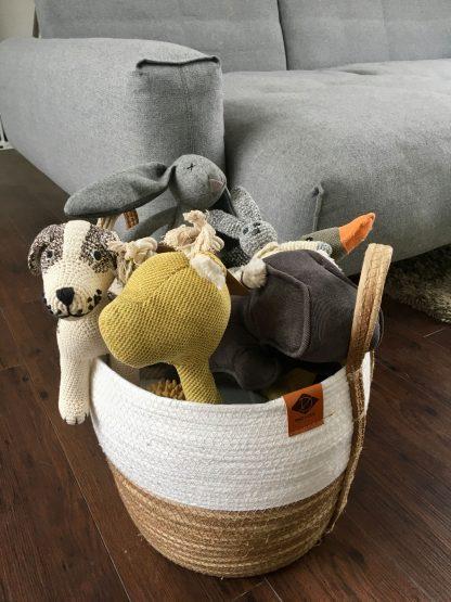 mehrere Hundespielzeug in einem geflochtenen braun-weißen runden Korb